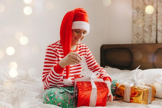 Счастливый мальчик в шляпе санта-клауса сидит на кровати с рождественским подарком. рождественский малыш, ребенок.