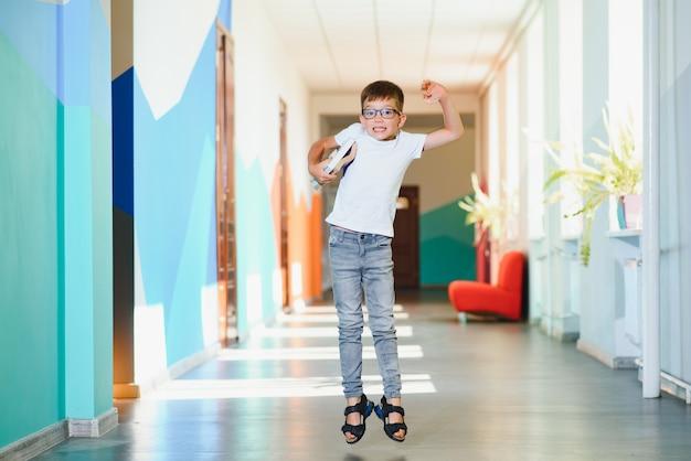 学校の廊下で幸せな少年。学校に戻る。