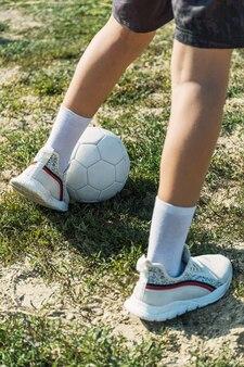 Счастливый мальчик в белой футболке, тренируясь на спортивной площадке с мячом.