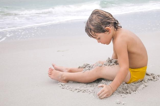 행복 한 소년 해변에서 모래를 놀고있다. 바다에서 놀고 수영하는 아이. 휴가. 해변에서 어린이를위한 활동. 기쁨과 행복
