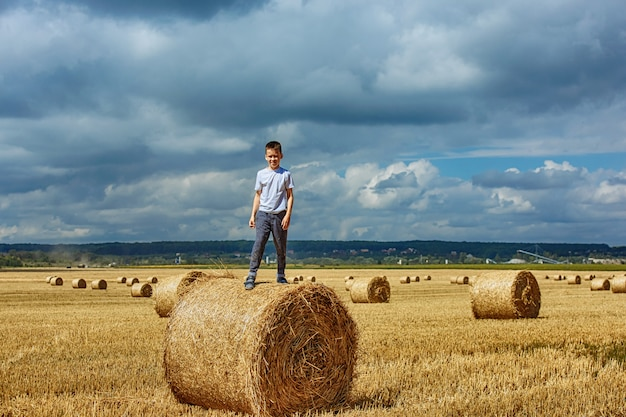 A happy boy is standing on a bale of hay.