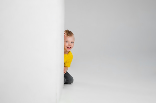 Счастливый мальчик, изолированные на стене. выглядит довольным, бодрым. copyspace детство, образование, эмоции, концепция выражения лица. прыгать высоко, играть весело