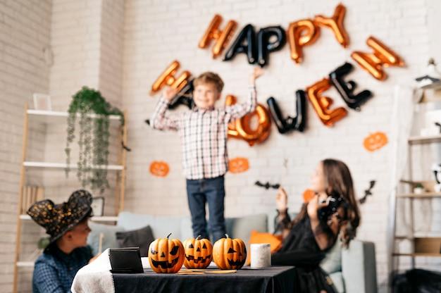 소파에서 점프하는 행복한 소년과 그의 친구 할로윈 파티 컨셉 옆에