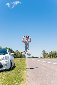 Happy boy jumping on the road next to car