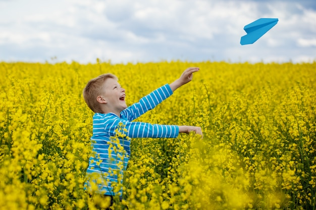 Happy boy leaning and throwing blue paper airplane on bright sunny day in the yellow field