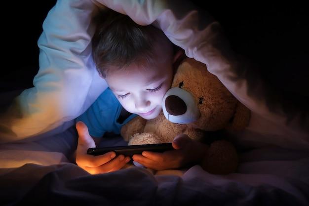 幸せな少年は、毛布の下のベッドでおもちゃのクマと、暗闇の中でデジタルタブレットのスマートフォンデバイスを使用して横たわっています