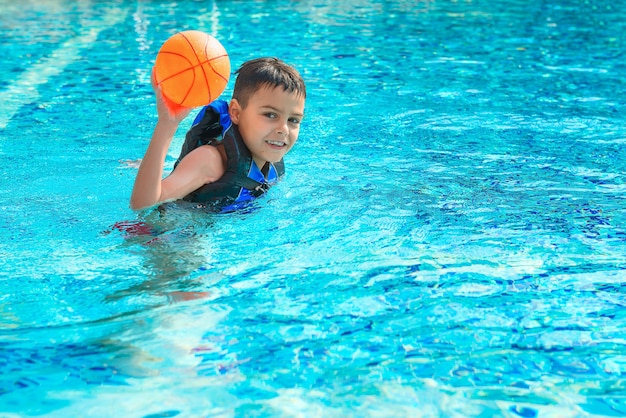 Happy boy in life jacket is playing with ball in pool. childhood, vacation, recreation, healthy lifestyle theme