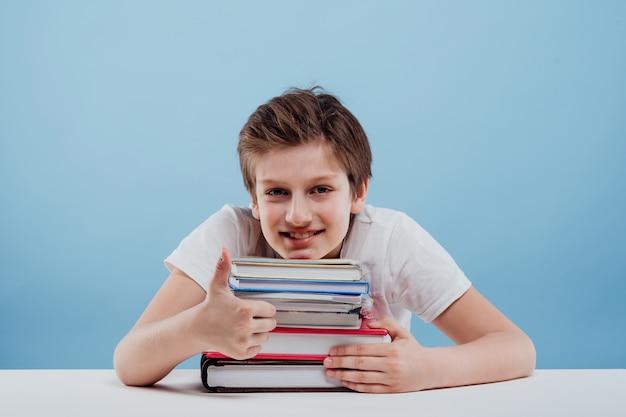 Счастливый мальчик смотрит в камеру с большим пальцем вверх, сидя за столом, изолированным на синем фоне