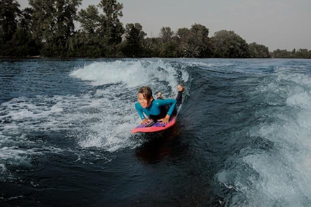 ウェイクボードの上に横たわると川を泳いで幸せな少年