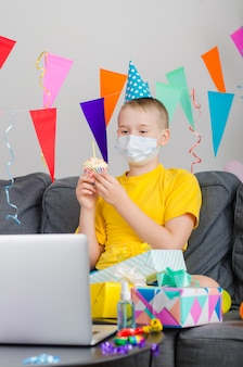 Happy boy in medicine face mask celebrates birthday by video call to laptop