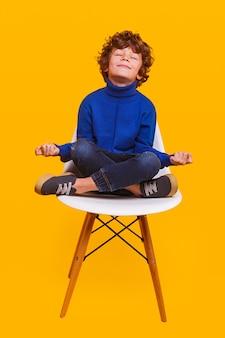 Счастливый мальчик медитирует на стуле