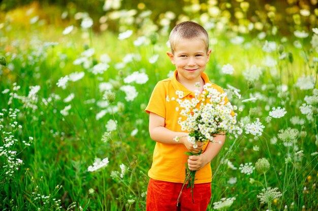 花の花束を持って花が畑に幸せな少年