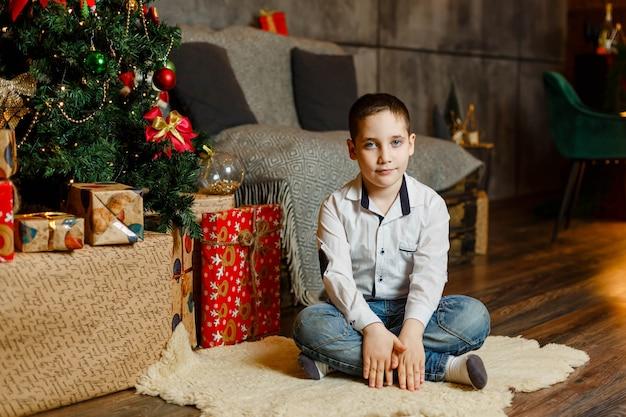 Счастливый мальчик открытие подарки в канун рождества. красивый мальчик сидит на полу рядом с рождественской елкой. малыш отмечал зимние праздники. рождество - пора подарков. семья и образ жизни