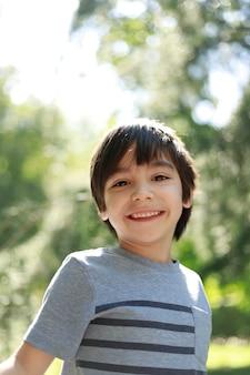 Happy boy in the park looking ay camera
