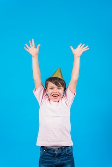 Happy boy in party hat with arm raised against blue background
