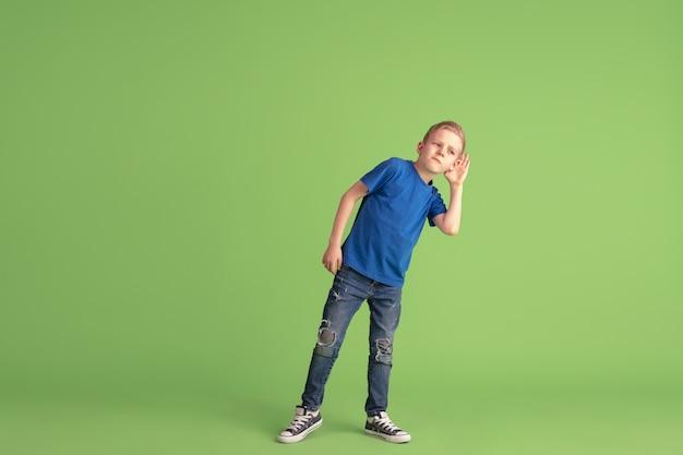 Счастливый мальчик играет и веселится на зеленой стене студии