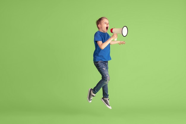 緑のスタジオの壁で遊んで楽しんでいる幸せな少年