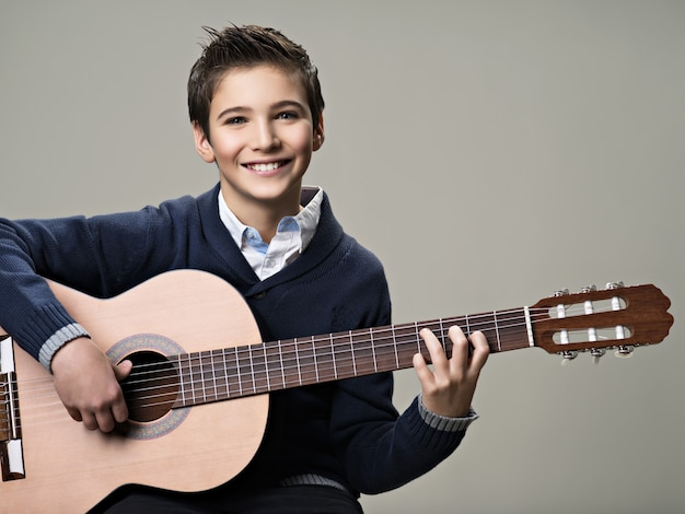Счастливый мальчик играет на акустической гитаре.