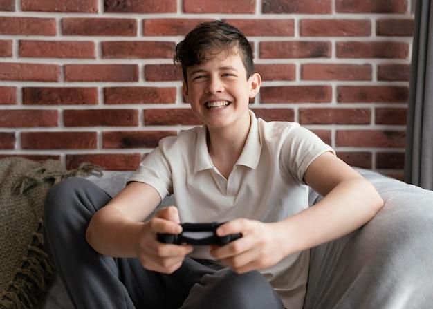 Счастливый мальчик играет в видеоигру средний выстрел