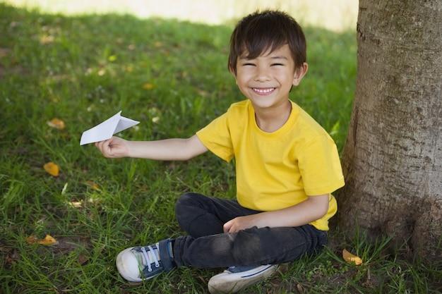 公園で紙飛行機で遊んでいる幸せな男の子
