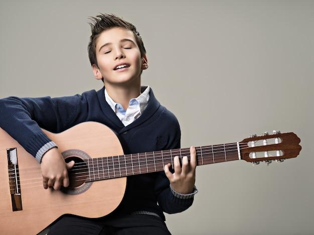 Счастливый мальчик с удовольствием играет на акустической гитаре.