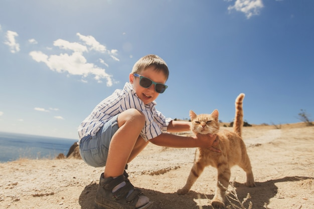 Happy boy playing with red cat
