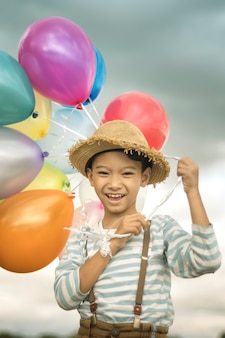 Happy boy plays with colored balloons on the beach having great holidays time on summer.