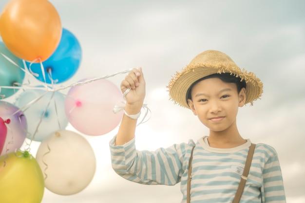 행복 한 소년 여름에 좋은 휴가 시간을 보내고 해변에서 컬러 풍선으로 재생합니다. 엘
