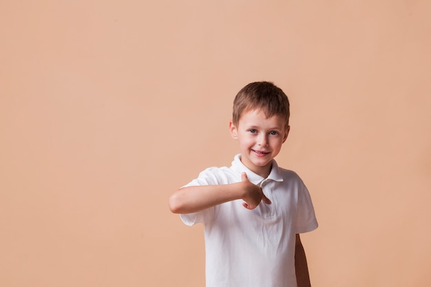Happy boy pointing finger at himself standing near beige wall