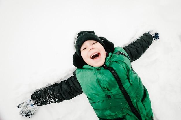 Счастливый мальчик портрет прогулки, игры и лежать в снегу в зимнем парке, концепция праздника. эмоции счастья. плоская планировка, вид сверху.