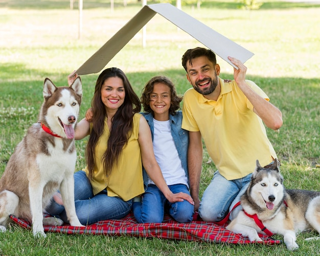 Счастливый мальчик позирует в парке с собаками и родителями
