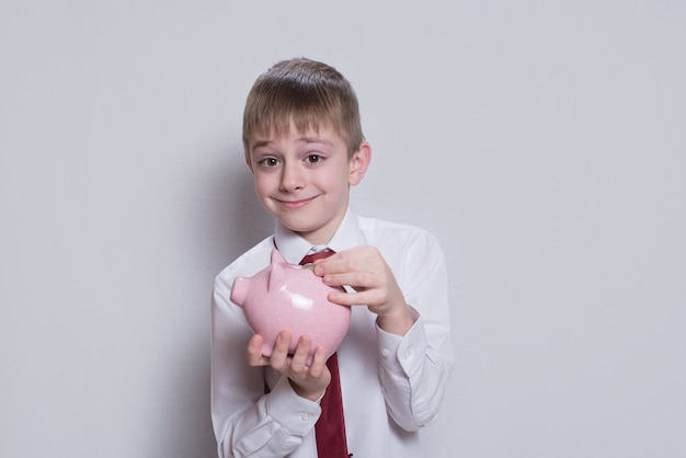 Happy boy puts a coin in a pink piggy bank. business concept. light background