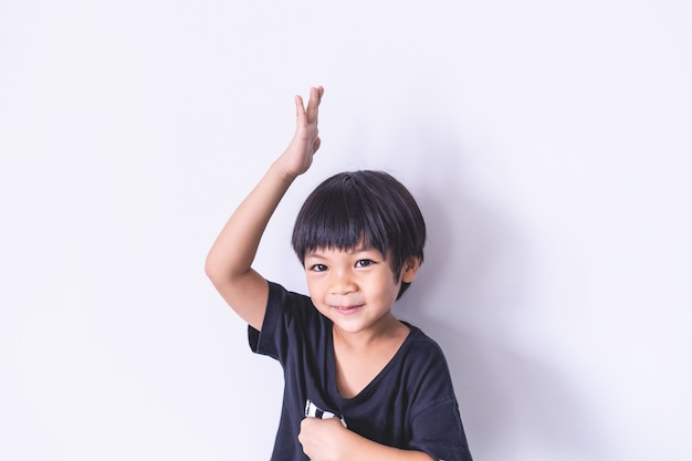 Happy boy raise his hand up on white background