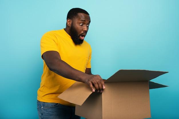 幸せな少年は、オンラインショップの注文からパッケージを受け取ります。幸せで驚きの表情。