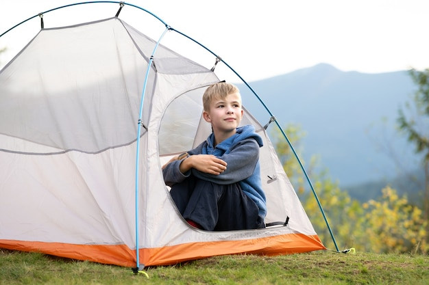 Happy boy resting alone in a tourist tent at mountain campsite enjoying view of beautiful summer nature. hiking and active way of life concept.