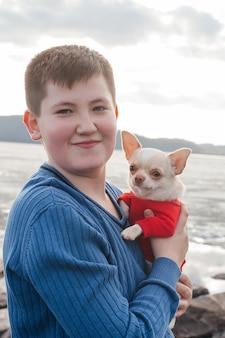 A happy boy on the river bank holds a chihuahua dog in his arms and smiles. a child with a dog in nature.