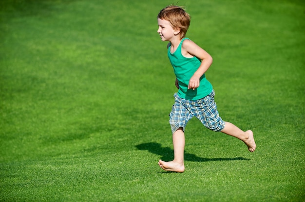 Happy boy running at the green golf course at sunny day