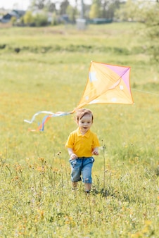 Happy boy runs outdoors with a kite