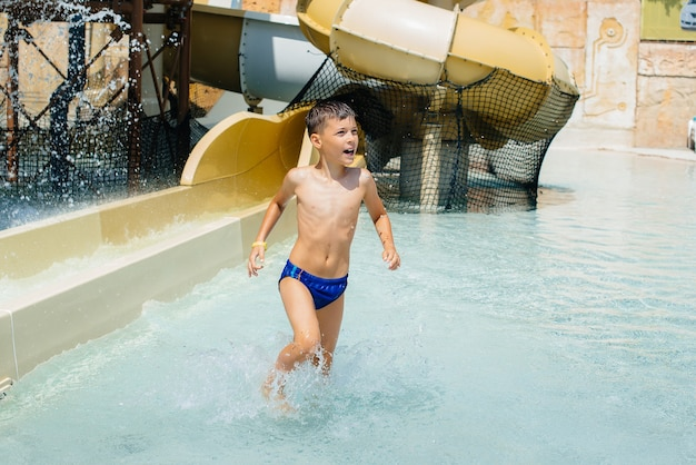 A happy boy of seven years old descends from the slides in the water park. happy vacation vacation. summer holidays and tourism.