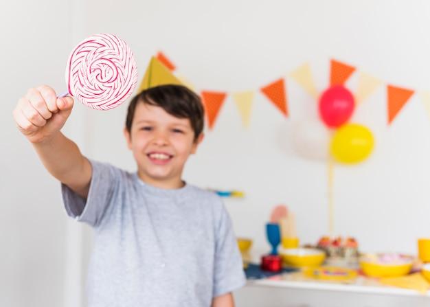 Happy boy showing sweet swirl lollipop standing at home