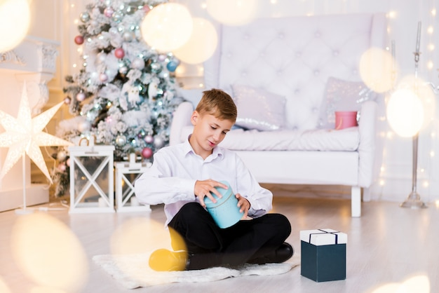 Happy boy sitting on the floor opens a gift in a christmas atmosphere bright photo