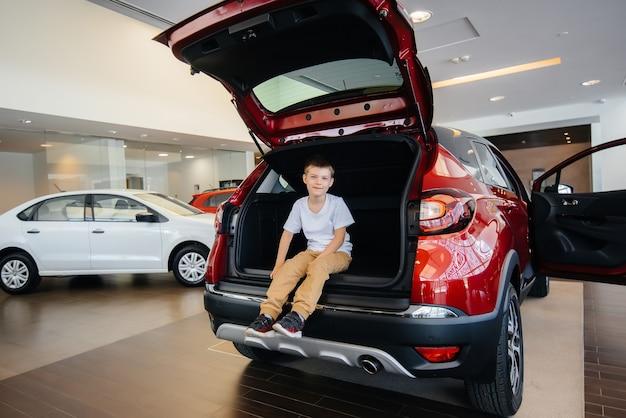 Счастливый мальчик сидит в багажнике новой машины в автосалоне