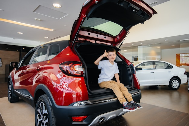 ディーラーで新車のトランクに座っている幸せな少年