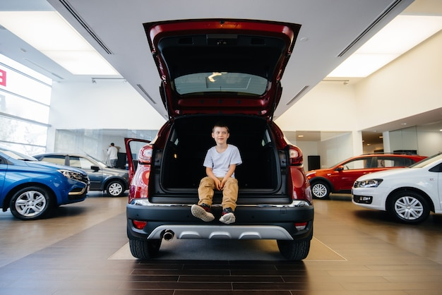 Happy boy sitting in the trunk of a new car at a dealership. buying a car.