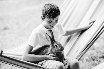Happy boy sitting with rabbit in hammock