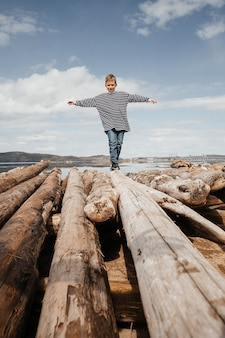 A happy boy in a striped vest walks along the logs to the shore. the boy tries to keep his balance as he walks over the logs. weekend rest.
