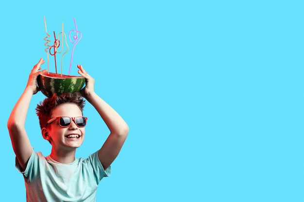 A happy boy in sunglasses holding watermelon with cocktail tubes on head on blue background