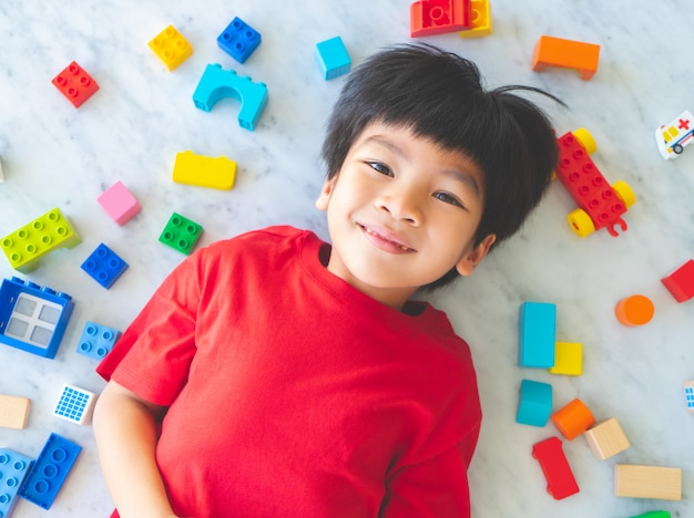 Happy boy surrounded by colorful toy blocks top view.