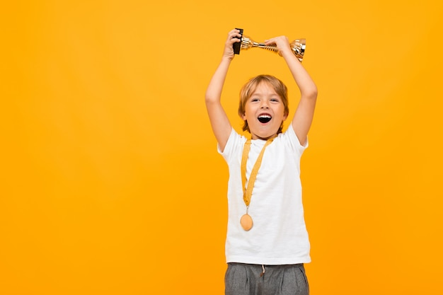 Happy boy in a t-shirt with a medal on his neck raises the winner's cup on yellow with copy space