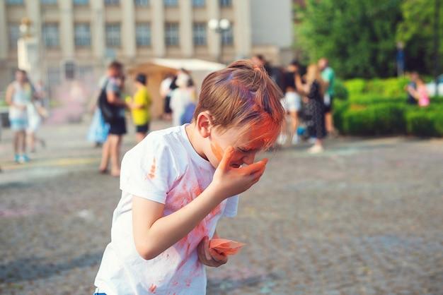 Счастливый мальчик бросает красочный порошок. концепция индийского фестиваля холи. милый мальчик раскрашен в цвета фестиваля холи. счастливое детство. празднование холи.